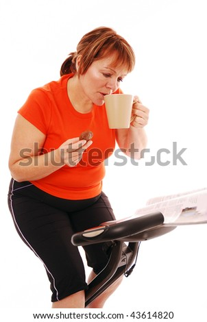 Woman taking a break reading and drinking while on exercise bike over white
