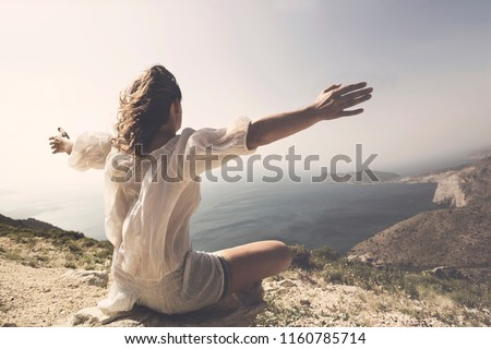 woman taking a breath in front of a spetacular view #1160785714
