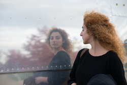 woman taking a passing look at reflection in side of American style diner like a huge mirror