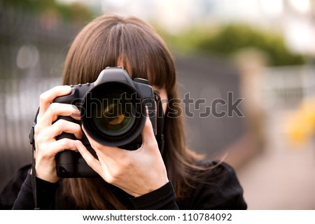 Woman taking a photo in the city during the day with bokeh background