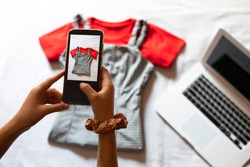 Woman taking a photo of an article of clothing to sell online. Concept of selling clothes online. Second-hand clothes.
