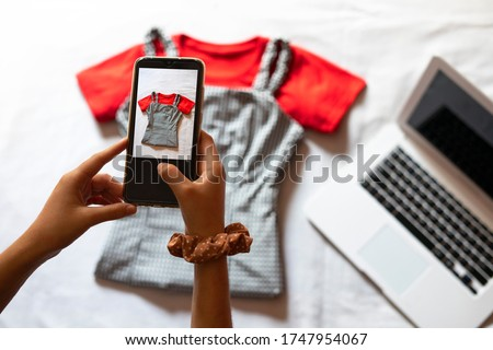 Woman taking a photo of an article of clothing to sell online. Concept of selling clothes online. Second-hand clothes. Foto stock ©