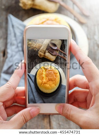 Woman taking a photo of Butter Cheese Cake by smartphone