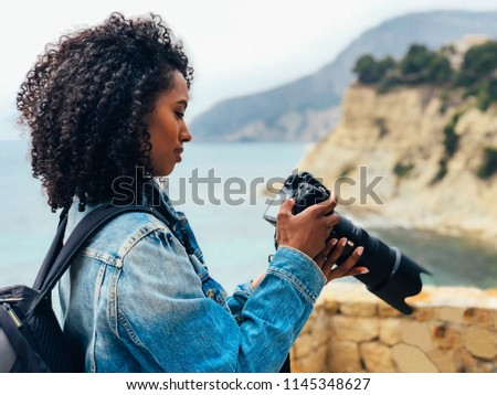 Woman taking a picture of a sea landscape with a professional camera