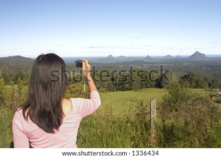Woman taking a picture of mountain view