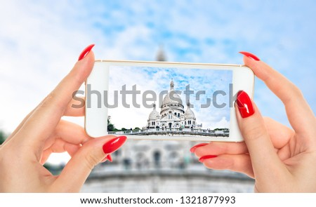 Woman taking a picture of Sacre-Coeur basilica (Basilica of the Sacred Heart of Jesus), Montmartre, Paris