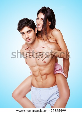 Woman Taking A Piggyback Ride on the back of a fit handsome young man, three quarter studio portrait on blue