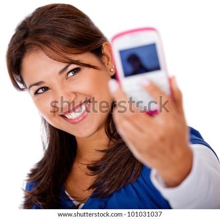 Woman taking a self portrait with her phone - isolated over white
