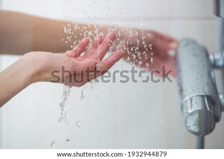 Woman taking a shower at home - female hands tryimg the temperature of water in shower Foto stock ©