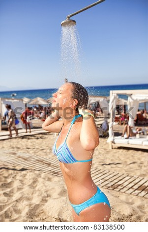 woman taking a shower on beach , really relaxing time