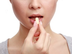Woman taking a tablet. Close up hand with a pill and the mouth, isolated on white background