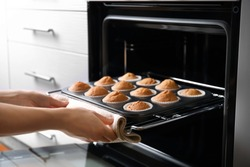 Woman taking baking tray with cupcakes from oven