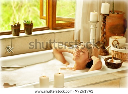 Woman taking bath, happy female relaxing at spa resort, young healthy girl at vacation, lady lying down in hot water, travel to luxury spa - stock photo