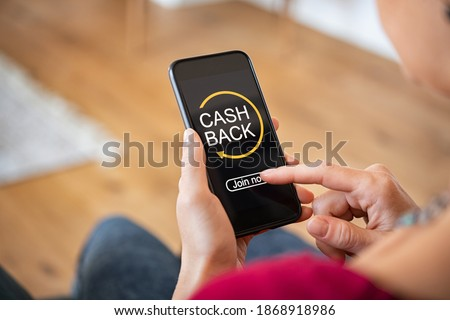 Woman taking benefit of cash back using smart phone, shopping and money refund concept. Close up hand holding smartphone with button to get started the cashback.  Foto d'archivio ©