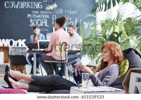 Woman taking business rest break reading newspaper in comfortable position