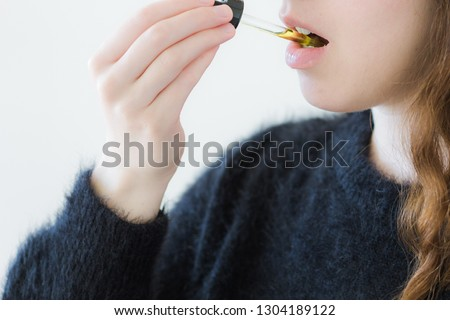 Woman Taking CBD Oil Under Tongue