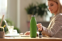 Woman taking green thermos bottle at workplace, closeup