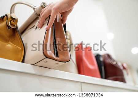 Woman taking her favourite handbag from collection of expensive fashinable bags standing on the shelf ストックフォト ©