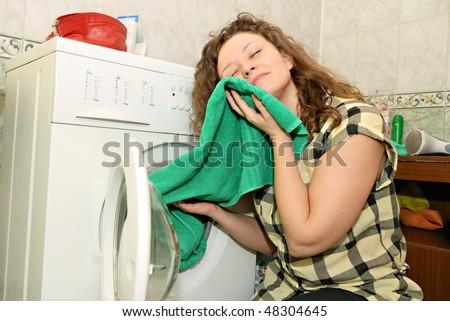 woman taking linen from washing machine
