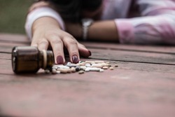Woman taking medicine overdose and lying on the wooden table with open pills bottle