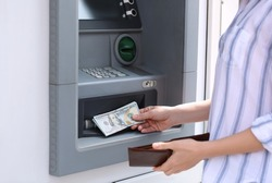 Woman taking money from cash machine outdoors, closeup