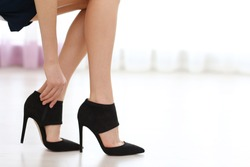 Woman taking off black high heels shoes.