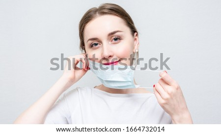 Photo of  Woman taking off her medical mask, portrait, close up, white background, 16:9