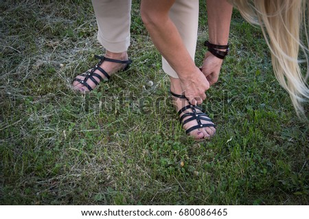 6b73bdc74f41 Woman taking off shoes in green grass to go barefoot and enjoy vacation day  in summer