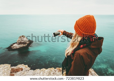Woman taking photo by smartphone of cold sea view Travel Lifestyle concept adventure vacations outdoor. Girl sharing photos in social media using modern technology communication gadget