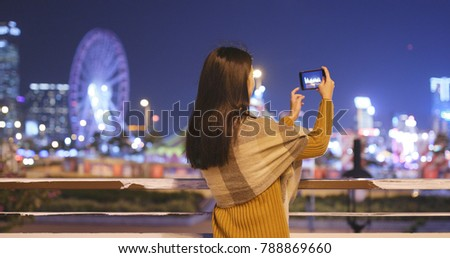 Woman taking photo in the city on cellphone at night