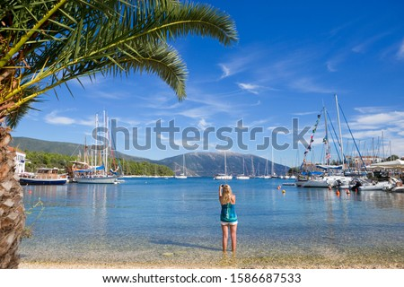 Woman, taking photo of boats, on sunny beach