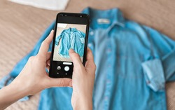 Woman taking photo of denim shirt on smartphone
