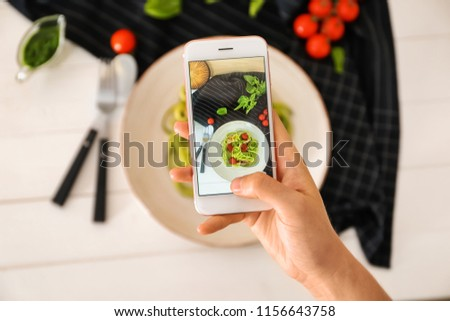 Woman taking photo of zucchini spaghetti with mobile phone, closeup