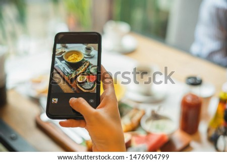 Woman taking photo on cellphone on dish. Woman taking photo of food with mobile phone in morning.