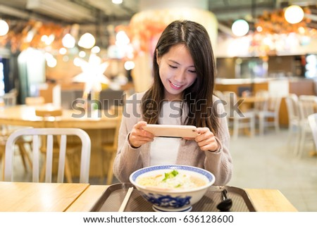 Woman taking photo on her noodles in restaurant
