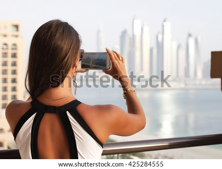 Woman taking photo photographing using smart phone in Dubai, UAE. Young tourist taking pictures on holidays.