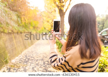 Woman taking photo with cellphone on the autuman landscape