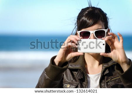 Woman taking photo with cellphone on the beach on spring. Happy girl on vacation taking picture on sea background.