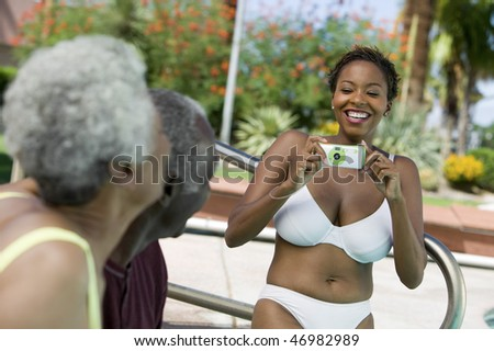 Woman Taking Picture at Poolside Barbecue