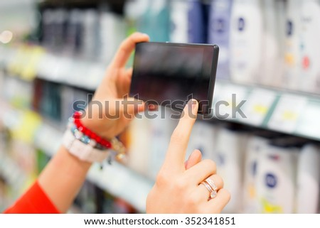 Woman taking picture in supermarket