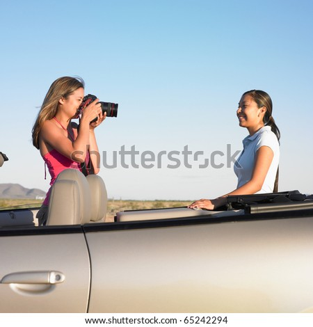 Woman taking picture of friend in convertible