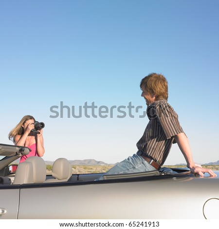 Woman taking picture of man sitting in convertible