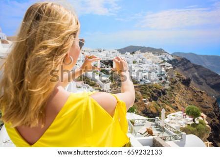 Woman taking picture of Santorini. #659232133