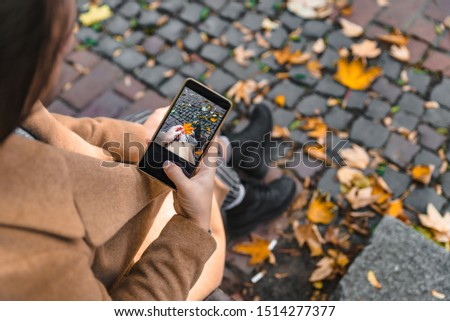 woman taking picture on phone of yellow maple leaf autumn season
