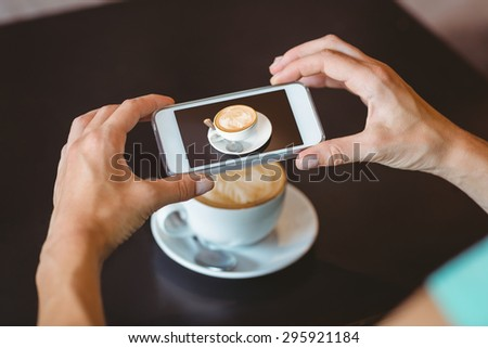 Woman taking picture with her smartphone at the cafe