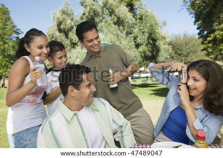 Woman Taking Pictures at a Picnic