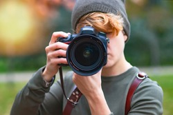 Woman taking pictures outdoors with analog camera, close up lens, photographer.