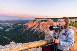 Woman taking pictures photos of view from Paria overlook of hoodoos rock formations in Bryce Canyon National Park at sunset with tripod and camera
