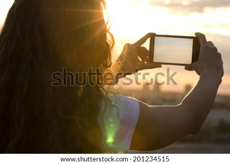 Woman taking pictures with her smartphone at sunset