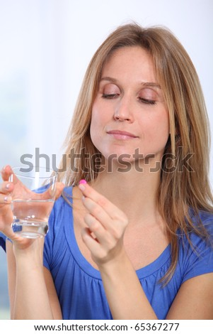 Woman taking pills to ease migraine